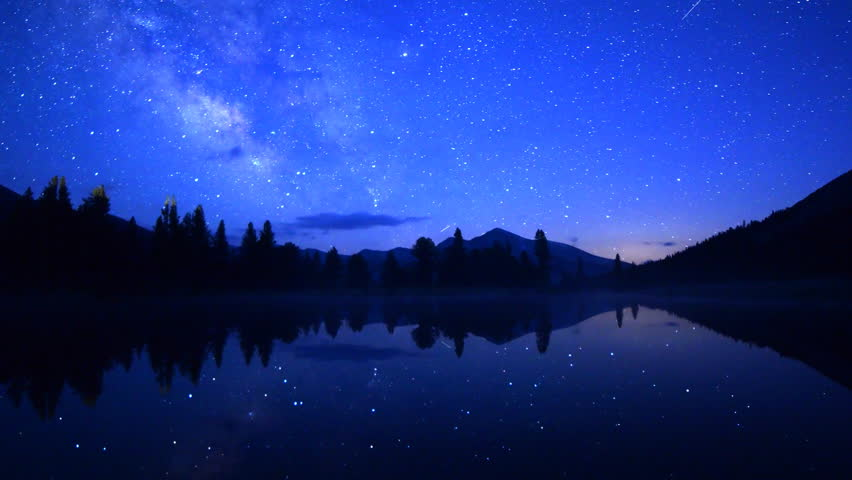Astrophotography Time-lapse footage of milky way galaxy spanning over reflective alpine lake in Yosemite National Park, California -Long Shot-