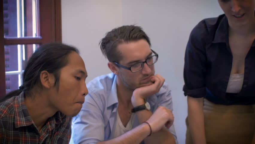 A diverse group of young professionals work together on a creative project