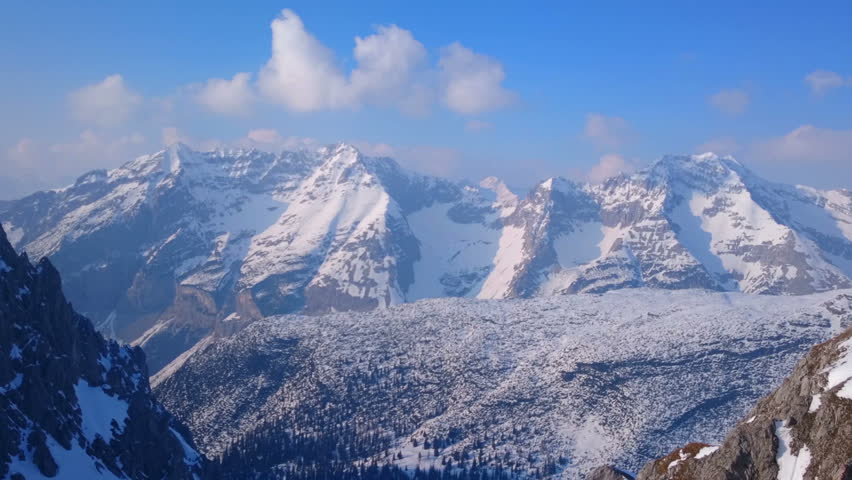 Spectacular horizontal panorama of winter mountains. Snowy hills on a sunny day