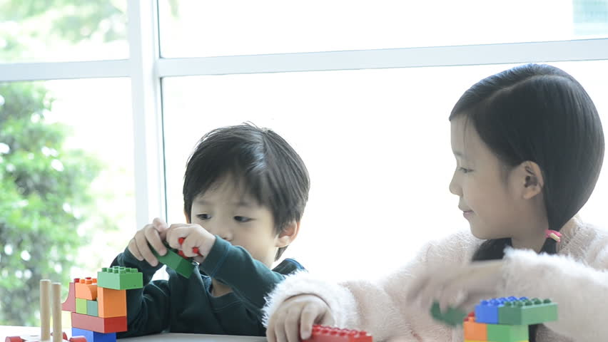 Little asian children playing with colorful construction blocks - HD stock video clip