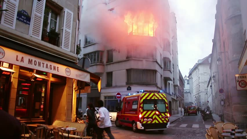 Fire Truck arriving after a huge fire is declared in central Paris. 4 OCTOBER 2015 - PARIS, FRANCE; An apartment explodes and catches fire, breaking all the windows and killing one person.