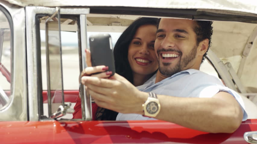 Happy young man and woman smiling, taking picture with cell phone camera for social network from red vintage convertible car