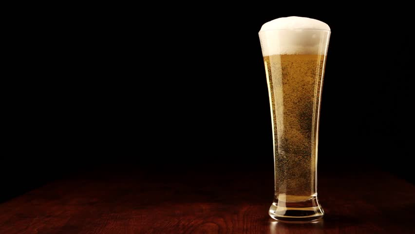 Beer in glass on a wooden table - HD stock footage clip