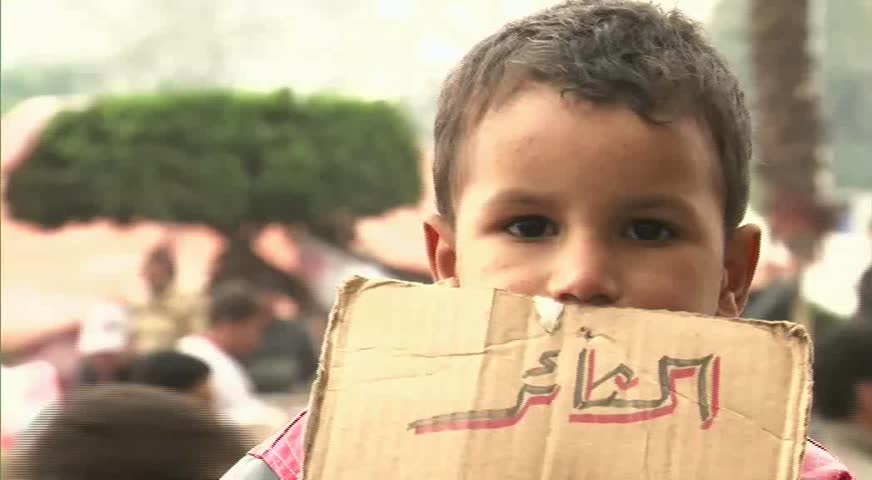 CAIRO - CIRCA JAN 2011: Child with protesting label, Tahrir Square, circa January 2011, Cairo, Egypt. Tahrir Square was the focal point of the 2011 Egyptian Revolution where demonstrations grew to 250,000 plus people by day 6, January 31, 2011.