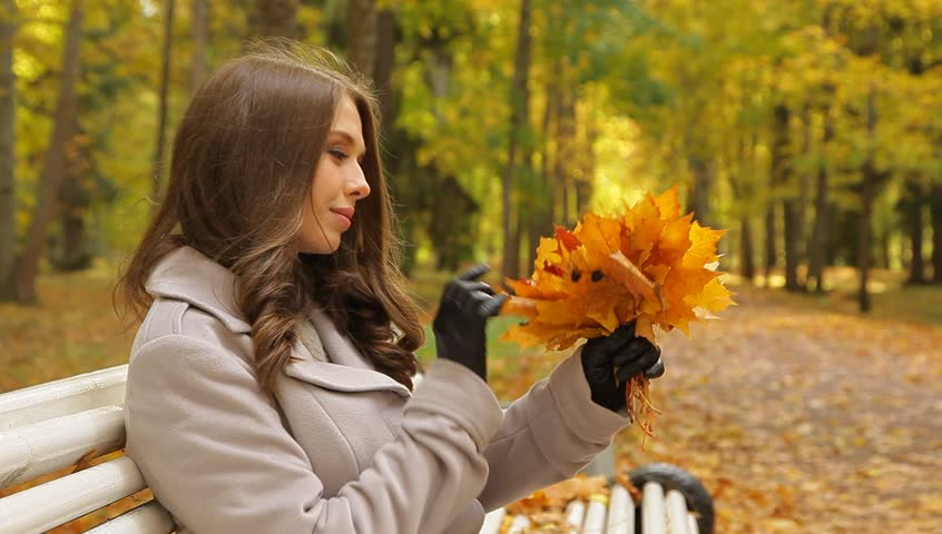 Portrait of a pretty woman  with maple golden leaves sitting on a bench in a beautiful autumn park waiting for someone.  - HD stock video clip