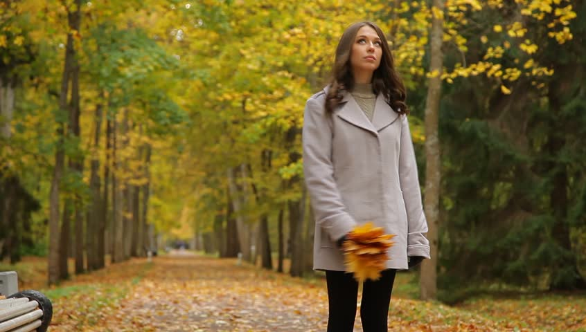 Pretty woman with maple golden leaves in a beautiful autumn park. She is walking, sitting on a bench, waiting for someone. - HD stock video clip