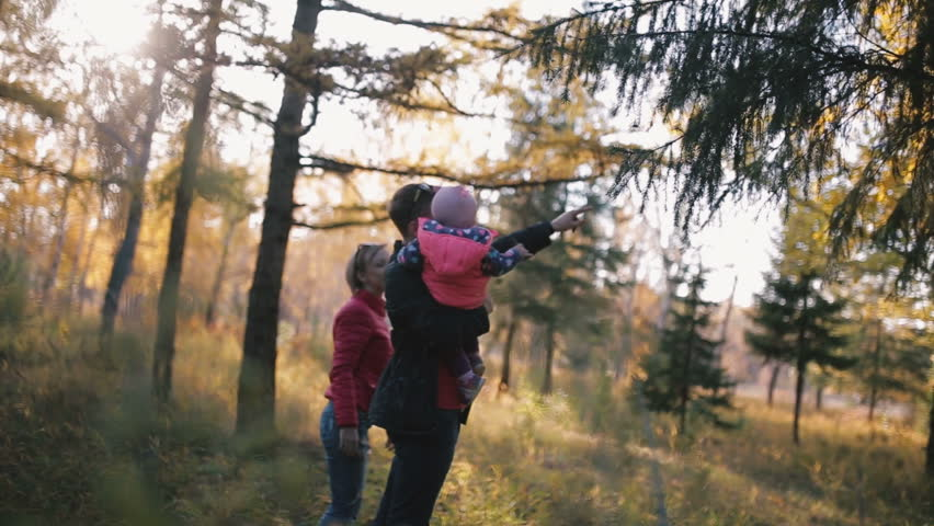 Happy family with a child in her arms walks in the woods. Shines autumn sun - HD stock footage clip