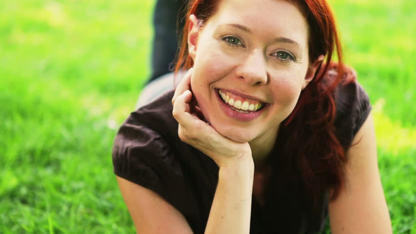 Happy redhead girl relaxing on green meadow in park - HD stock footage clip