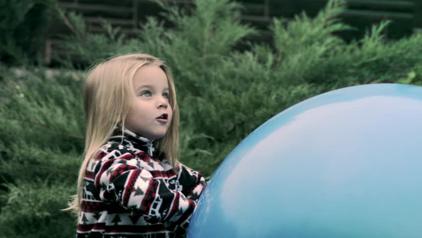 Happy birthday. Little girl playing with a giant inflatable ball.