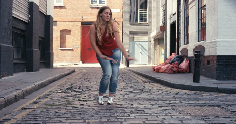 Contemporary street dancer woman happy funky urban dancing freestyle in the city - 4K stock footage clip