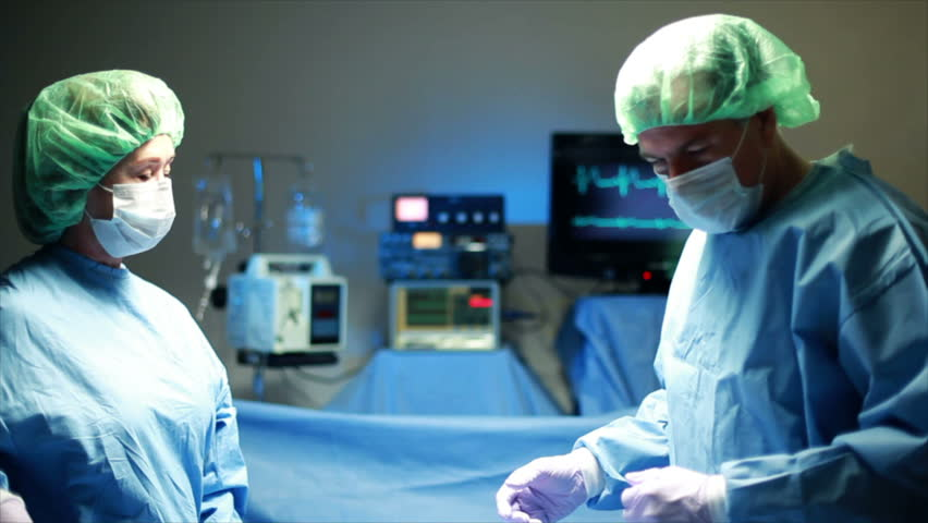 Two surgeons performing surgery are assisted by a surgical nurse. - HD stock video clip