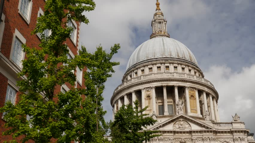 Close shot of the dome of St Pauls Cathedral in London. White clouds and blue sky. Original footage is 4K - 4K stock video clip