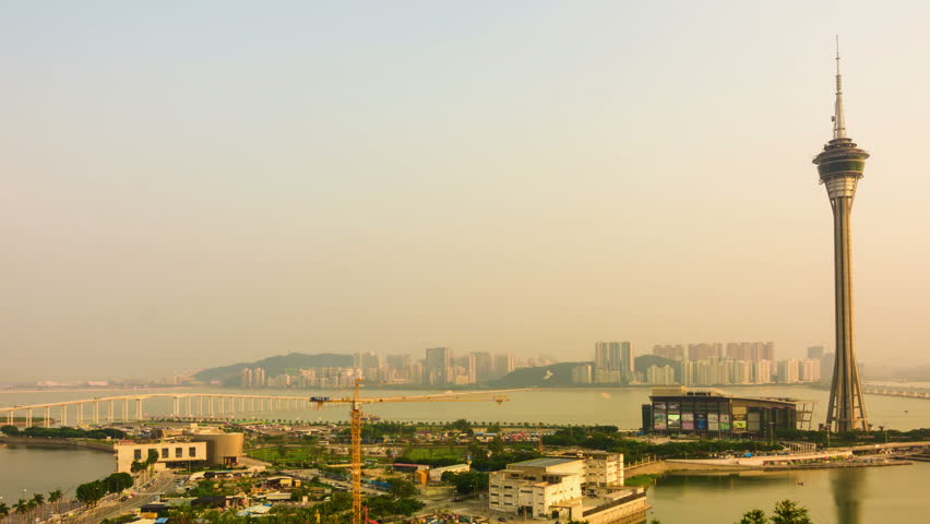 Urban landscape timelapse of Macau with famous traveling tower near river in Macao, Asia. zoomout