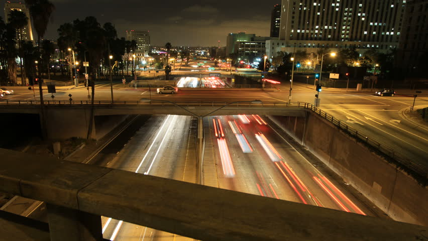 Sliding time-lapse shot above bridge railing revealing freeway traffic