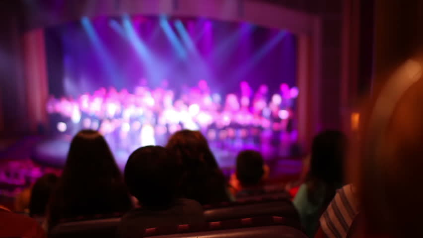 Audience members applaud at a stage show.