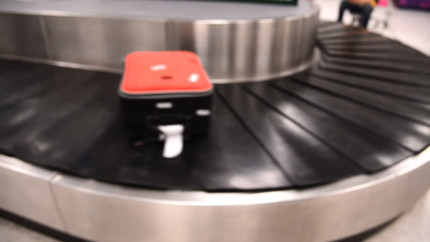 Blurred luggage passing by while on baggage carousel