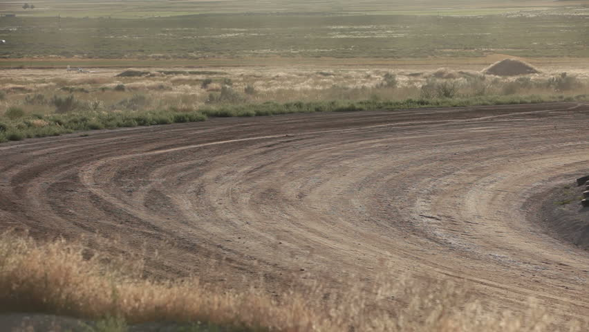 Race cars high speed on dirt oval course. Highly modified stock cars driving and racing on a very dirty and dusty track corner. High speed around dusty corner towards view. - HD stock video clip