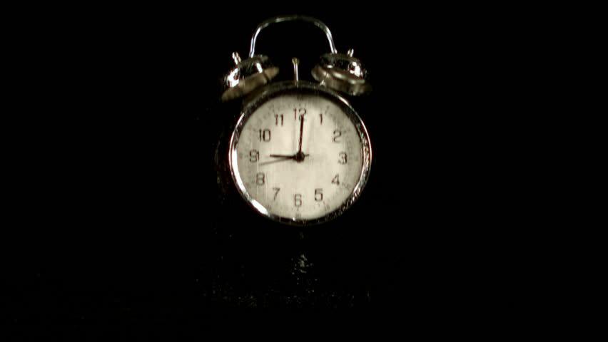Alarm clock falling on black background in slow motion