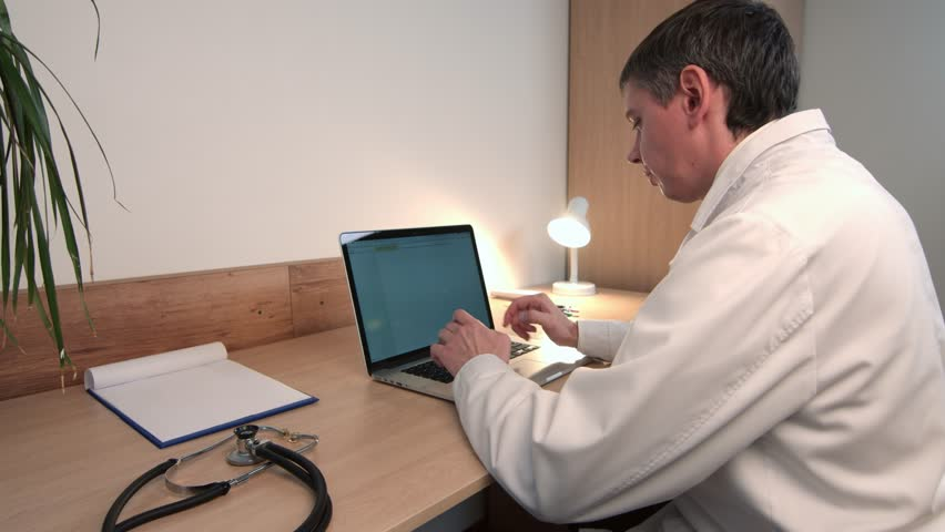 Male doctor student sitting and working on laptop alone in room