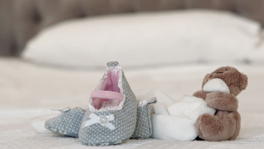 Baby shoes and teddy bear on bed at home