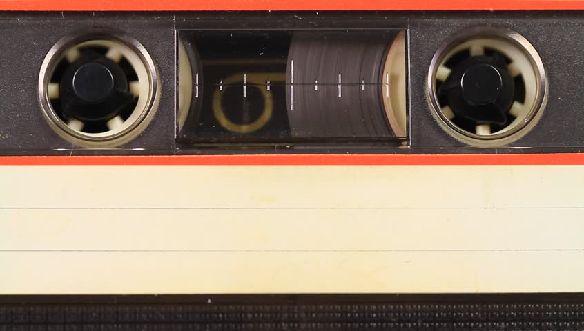 Inserting and recording tape cassette. Close up. Inserting cassette tape with a blank white label in use playing back in the tape recorder.