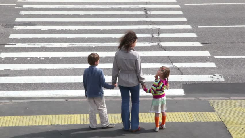 Mother and her two children, boy and girl, cross road at pedestrian crossing after car drove and other stopped to let them pass, then cars ride - HD stock footage clip