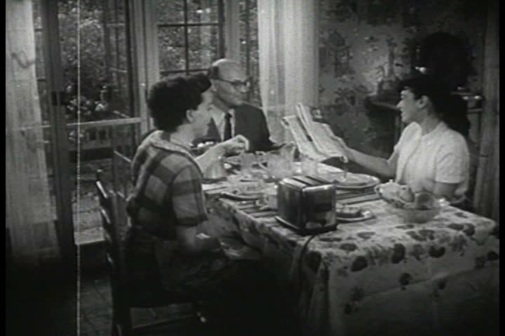 CIRCA 1950s - A young girl eats breakfast with her parents in the 1950s.