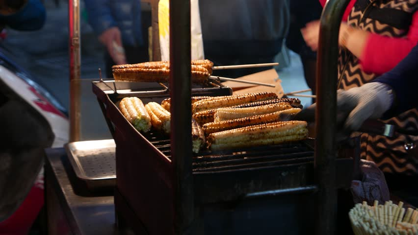 Grilling corn cobs on grate, close up view to roasted cob, flipped on the grill grate. Darker fired grains, traditional marketplace snack, freshly roasted corn