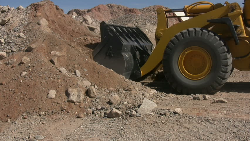 A front end loader getting a bucket full of gravel and dirt. - HD stock footage clip
