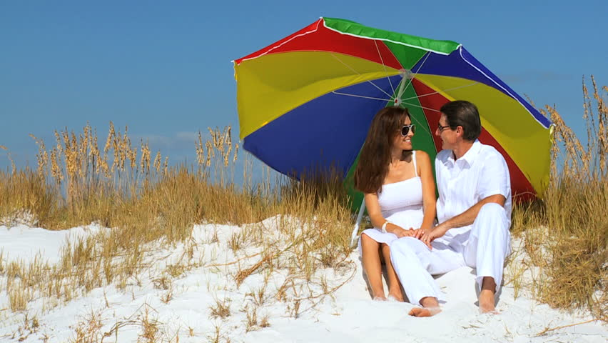 Happy healthy young couple getting shade under a sun parasol on the beach filmed at 60FPS - HD stock footage clip