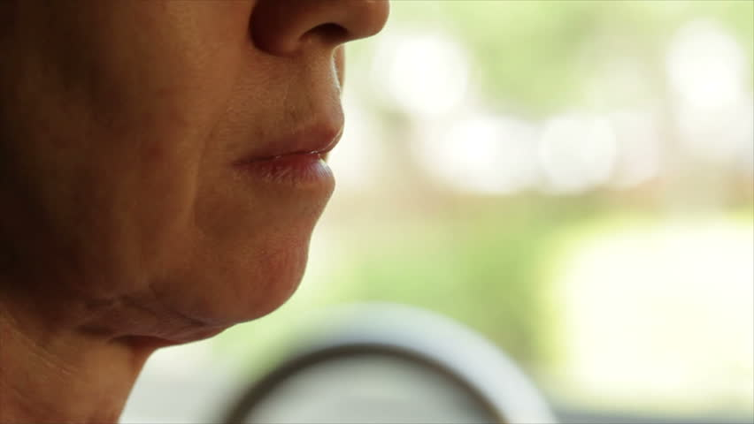 A close up of a mature woman standing in front of a window taking her prescription medication. - HD stock footage clip