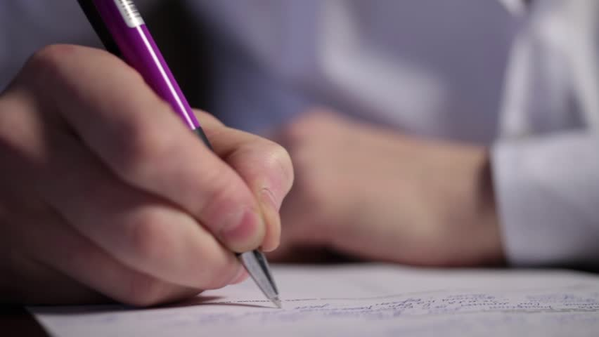 A man is writing description and signing a document with worries
