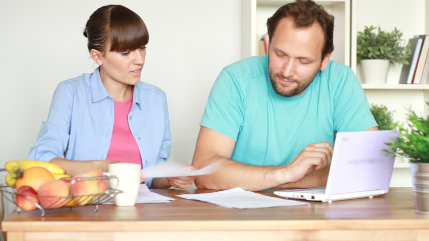 Happy couple calculating their bills by the table at home - HD stock video clip