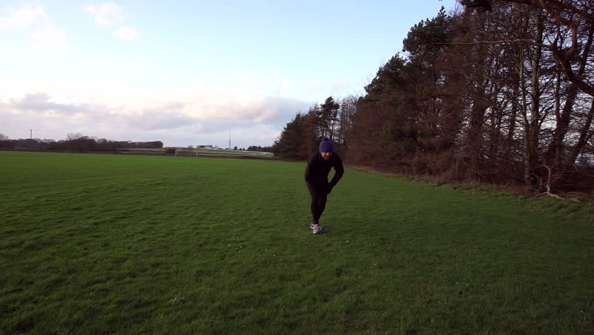 Male runner doing stretching exercises before setting off on run in field in winter time.