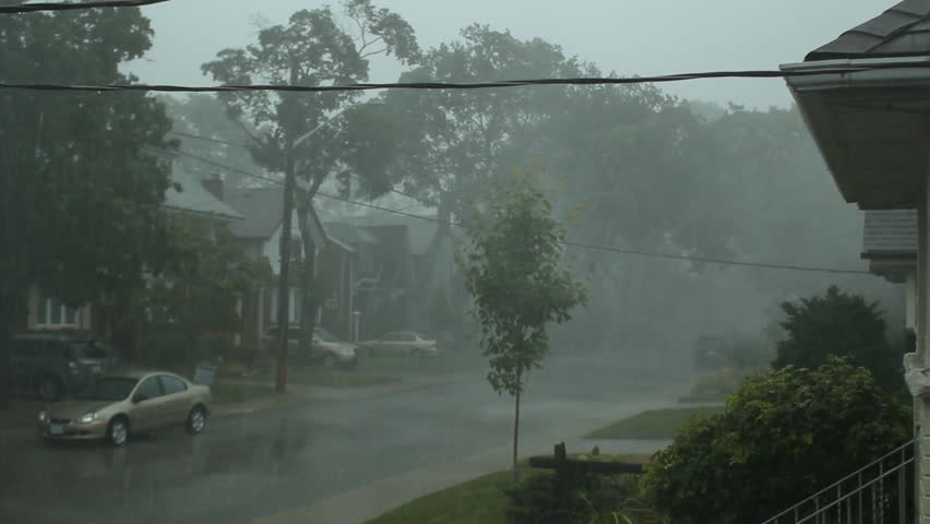 Scary suburban storm. Very strong summer storm with close to hurricane force winds. Thunder and lightning. Car drives down the street. East York, Ontario, Canada.