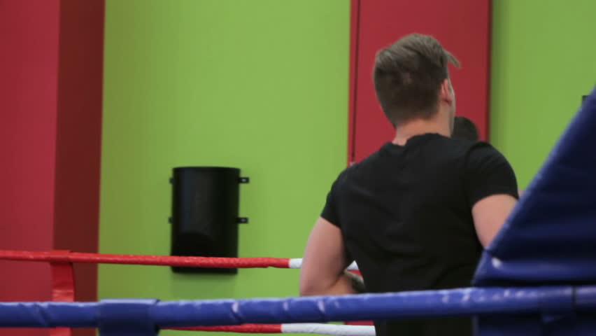 Boxing classes. Two men are training in the Boxing ring