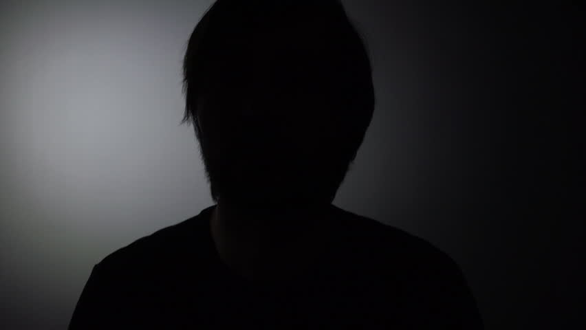 Person in witness protection program during police interview, silhouette of male giving statement to the police detectives during crime interrogation in dark room.
