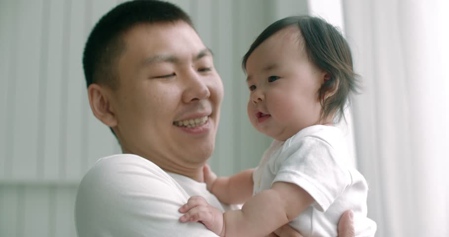 Young asian father lovingly holding up cute baby while they play together,slow motion,close up