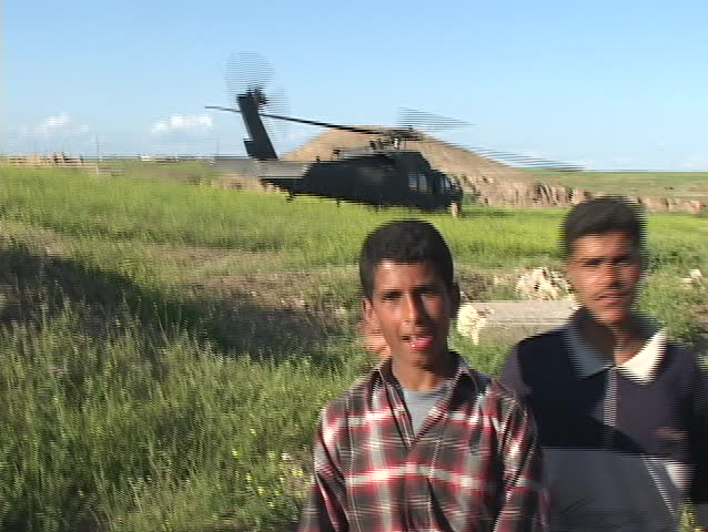 IRAQ - CIRCA 2003: Iraqi boys pose and give peace signs in front of a Blackhawk helicopter circa 2003 in Baghdad.