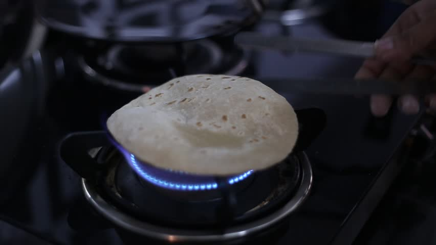 Indian thin bread called roti or chapati  made from wheat dough being baked on gas stove in home