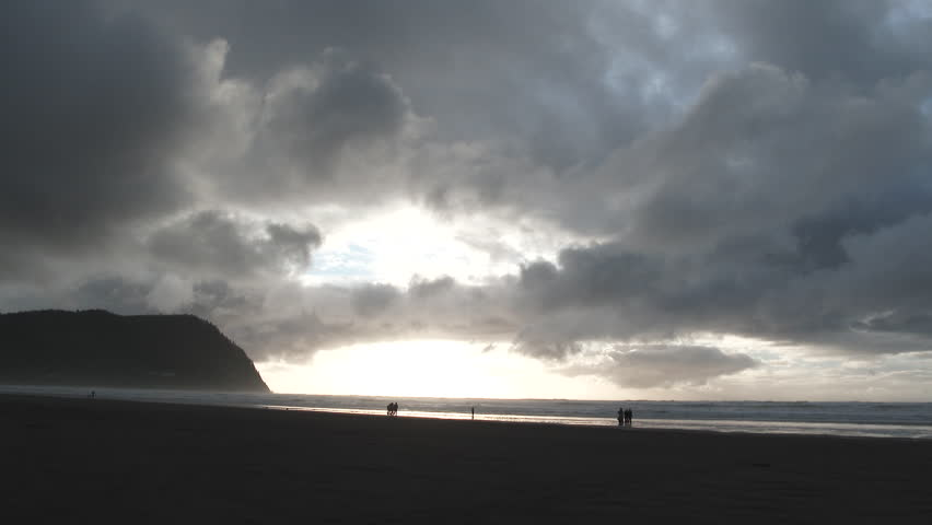 A break in the clouds gives light to people at the Oregon Coast in Seaside during sunset.
