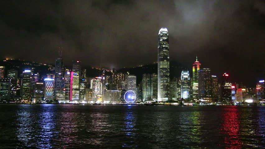 Skyscrapers and light display at night in Victoria Harbour of Hong Kong. Boats are in the harbour.