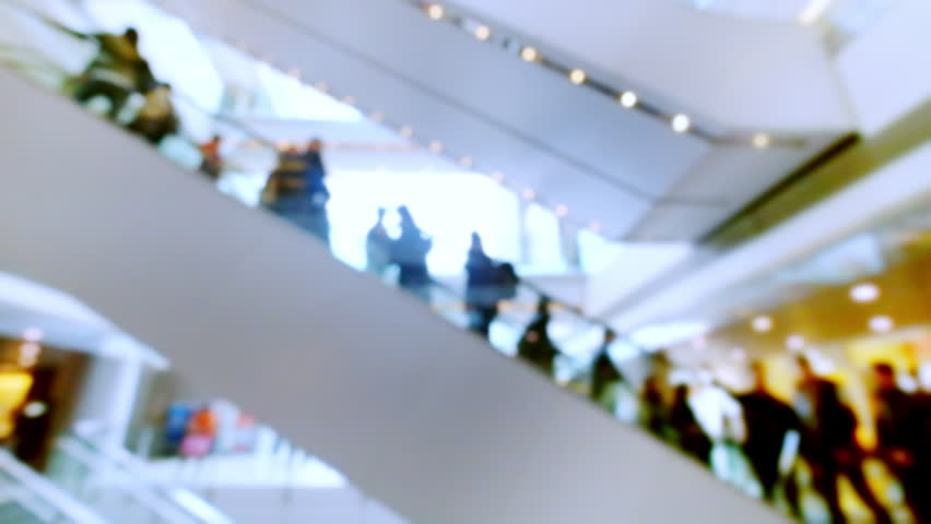 People on moving escalators at modern shopping mall, Hong Kong.  Blurred fast speed video, unrecognizable people