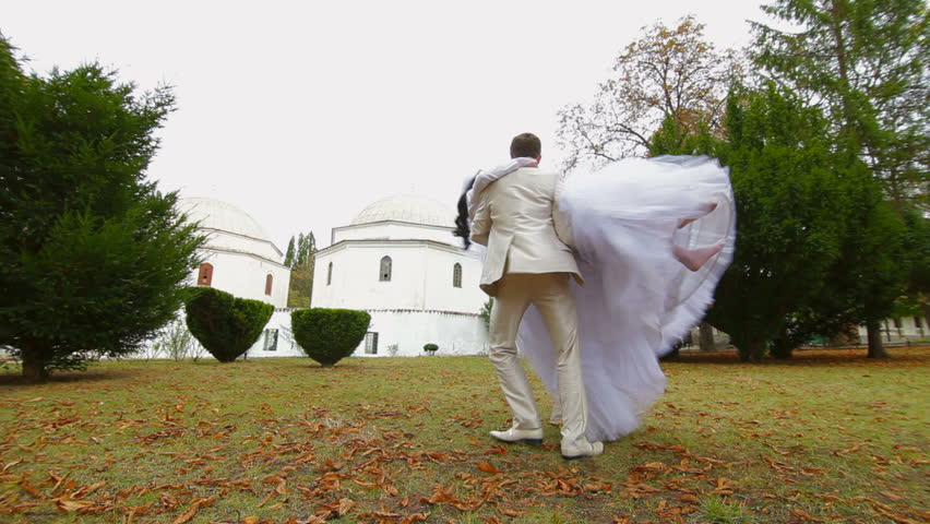 groom celebrating their wedding by spinning around the bride against the Muslim Mosque Bakhchisarai Palace (Hansaray, Khan's Palace) Bakhchisaray, Crimea, Ukraine - HD stock video clip