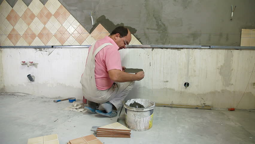 Working With Ceramic Tile : Man applying ceramic tile to a kitchen wall working with