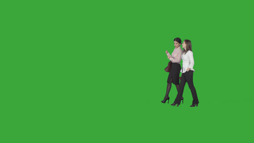 Two stylish business women, professionals, are chatting about their job & going at work to office. Green screen footage. File format - .mov, codec PNG+Alpha. Shutter angle -180 (native motion blur)