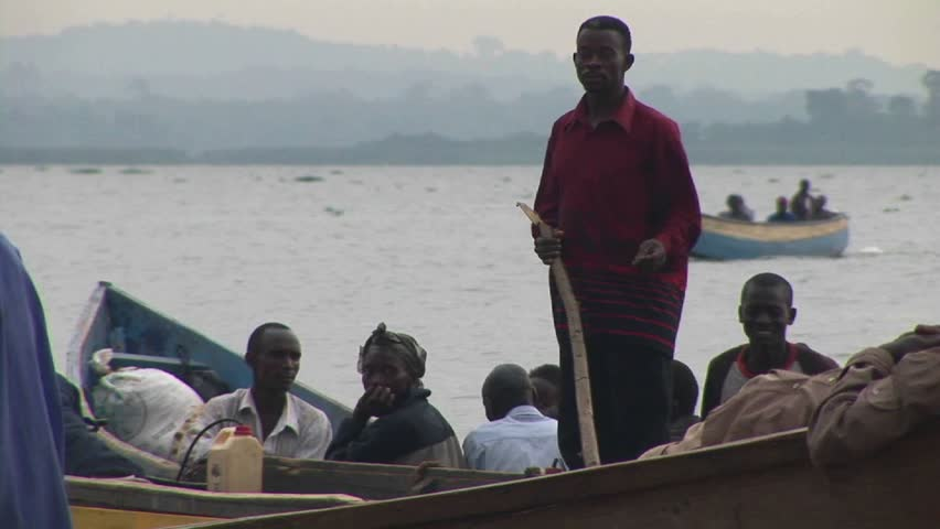 LAKE VICTORIA, UGANDA - CIRCA 2009: A man stands up on a boat and uses stick to navigate circa 2009 in Lake Victoria. - HD stock video clip