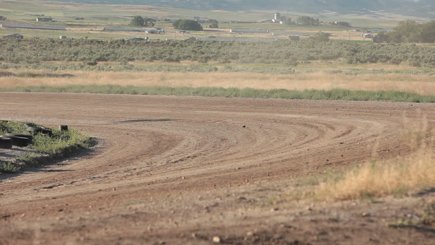 Race stock cars on dirt oval course. Highly modified stock cars driving and racing on a very dirty and dusty track corner. Warmup lap testing the road and track conditions. - HD stock video clip