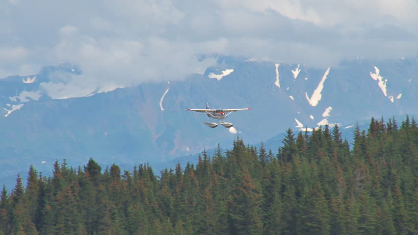 Descending from a cloudy sky with mountains in the background, a red and white floatplane lands on a lake with houses and other planes in the background. - HD stock footage clip