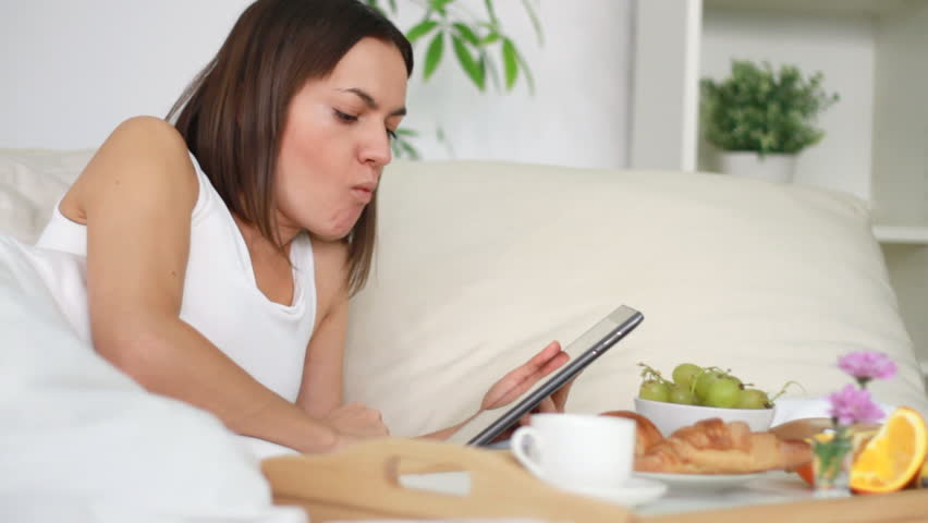 Woman eating breakfast in bed and surfing the net on digital tablet - HD stock video clip